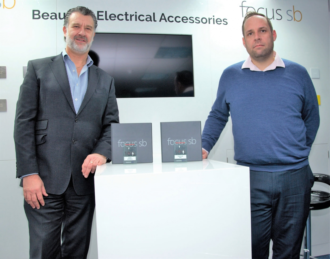 Image (from left to right): Gary Stevens, managing director, with Duncan Ray, supply chain and NPI manager, pictured with their Top 100 trophies in Focus SB's showroom in St Leonards on Sea, East Sussex.